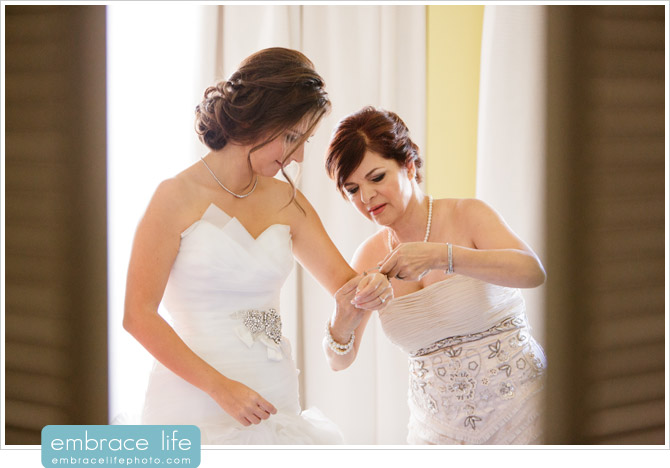 Mother of the bride fastening a sparkling diamond bracelet on her daughter's wrist