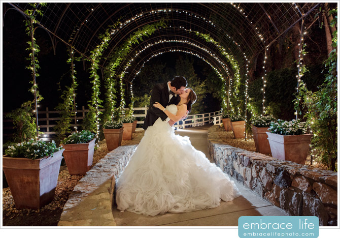 A night time portrait of the Bride and Groom under an arch with twinkle lights