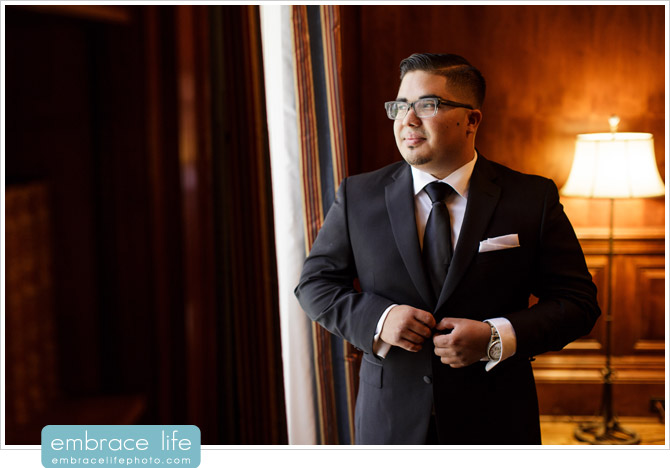 Groom Portrait at Athenaeum library buttoning suit jacket