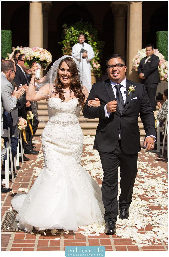 Bride and Groom celebrating as they walk down the aisle as husband and wife