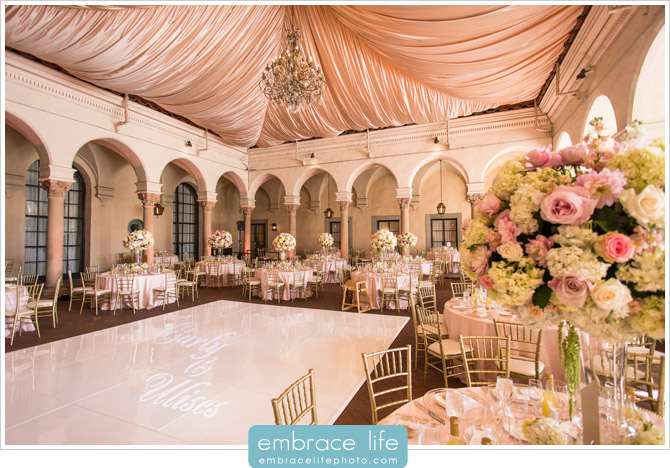 Gorgeous wedding reception featuring blush draping and custom monogram on white dance floor