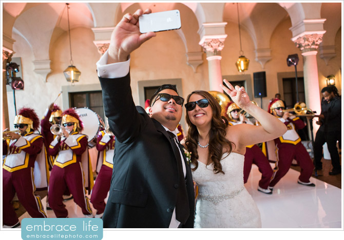 Bride and Groom taking selfie with USC Marching Band at their wedding reception